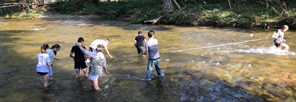 student researchers in river